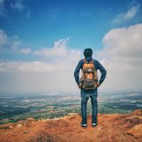 Man standing looking out from a mountain