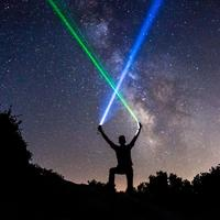 Man wielding blue and green lightsabers in the starry night sky