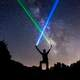 man-wielding-blue-and-green-lightsabers-in-the-starry-night-sky