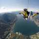 People skydiving above a lake