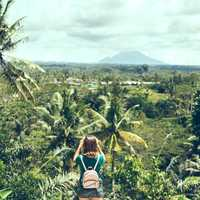 Woman traveler taking pictures of Batur volcano, tropical island