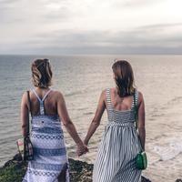 Two women holding hands overlooking the water