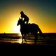 person-riding-horse-into-the-sunset