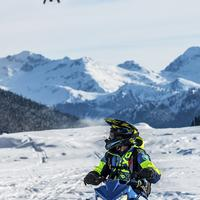Person riding snowmobile with mountains in the background