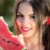 Pretty young woman eating watermelon