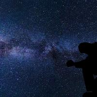 Silhouette of a man under the stars and galaxy