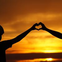 Silhouette of mother and daughter making a heart with hands during sunset