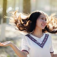 Smiling Asian Girl playing in the wind