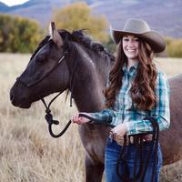 Smiling Cowgirl in hat with horse