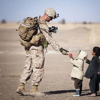 Soldier giving kids apple