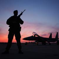Soldier standing guard over fighter plane free image