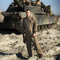 Soldier standing in front of a tank