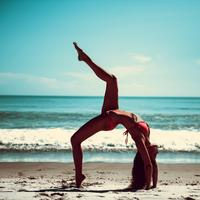 Somersault Pose of young women on beach