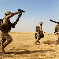 Three US Marines carrying weapons walking across the desert