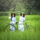 Two Asian Girls riding a Bicycle through a field