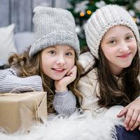 Two Girls sitting next to Christmas Tree and presents