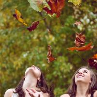 Two Girls throwing leaves into the air