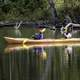 two-people-rowing-a-yellow-canoe