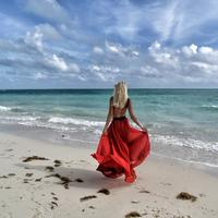 Woman by the seaside in backless red dress