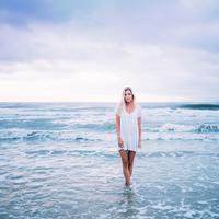 Woman Dressed in white standing in the sea