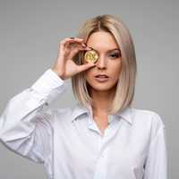 Woman holding Bitcoin up to eye