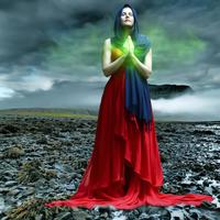 Woman Illuminated with green light under stormy clouds