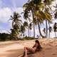 Woman in black Bikini on a tropical sandy beach