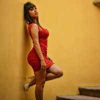 woman-in-red-dress-and-high-heels-next-to-wall