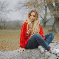 Woman in red sweater sitting on log