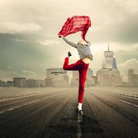 Woman leaping holding a red scarlet scarf for joy