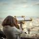 woman-looking-at-city-through-telescope