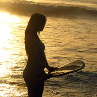 Woman on beach with surf board
