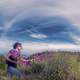 woman-picking-purple-flowers-under-the-clouds-and-sky