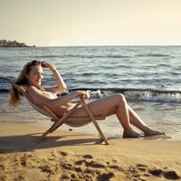 Woman sitting on the beach in a bikini in lawnchair