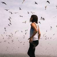 Woman standing under a flying flock of birds