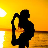 Woman stretching at sunrise on the beach