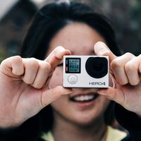 Woman taking photo with GoPro Camera