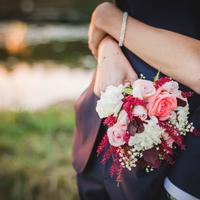 Woman with arms wrapped around a man with bouquet of flowers