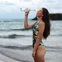 women-by-the-sea-in-bathing-suit-drinking-bottled-water