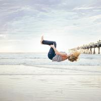 Woman doing a Backflip on the Beach