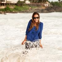 Women in Blue Shirt standing in shallow surf