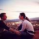 young-couple-sitting-together-on-a-hill-overlooking-a-town