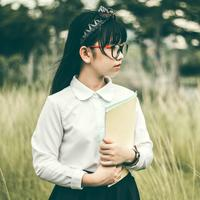 Young girl in glasses holding notebook
