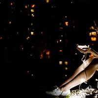 Young Women sitting at night looking at small lights