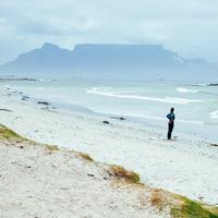 Surfer standing and looking at the waves in Cape Town, South Africa