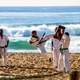 Karate Fighter Jump Kicking on Beach