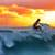 Man surfing a wave at sunset