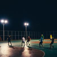 People playing soccer under the streetlamps