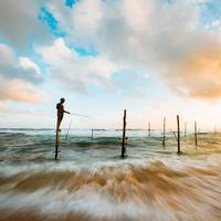 Time-Lapse landscape with fisherman under clouds and sky in Hikkaduwa, Sri Lanka