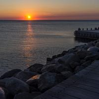 Sunset over the ocean at the shore and docks in Malmo, Sweden
